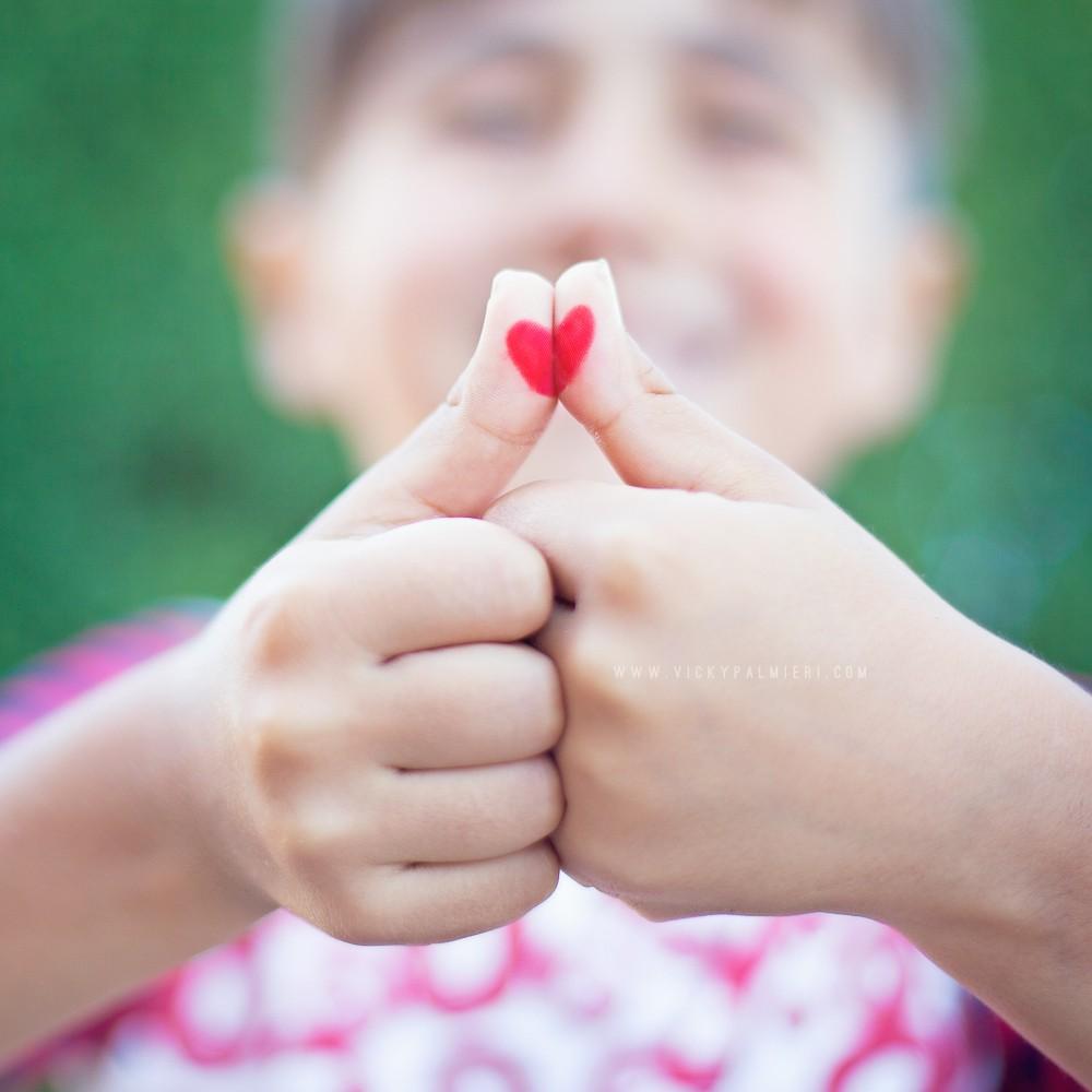 Love heart drawn on thumbs
