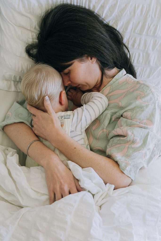 Mother laying in bed while cuddling with her 18 month old baby.